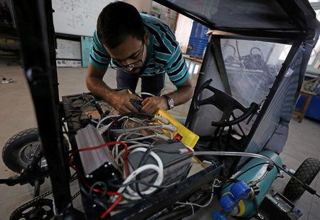 Islam Ibrahim, mechanical engineering student from Helwan University, checks electrical cables on the air-powered vehicle which he helped design to promote clean energy and battle increasing gas prices, in Cairo, Egypt August 7, 2018. Picture taken August 7, 2018. REUTERS/Mohamed Abd El Ghany