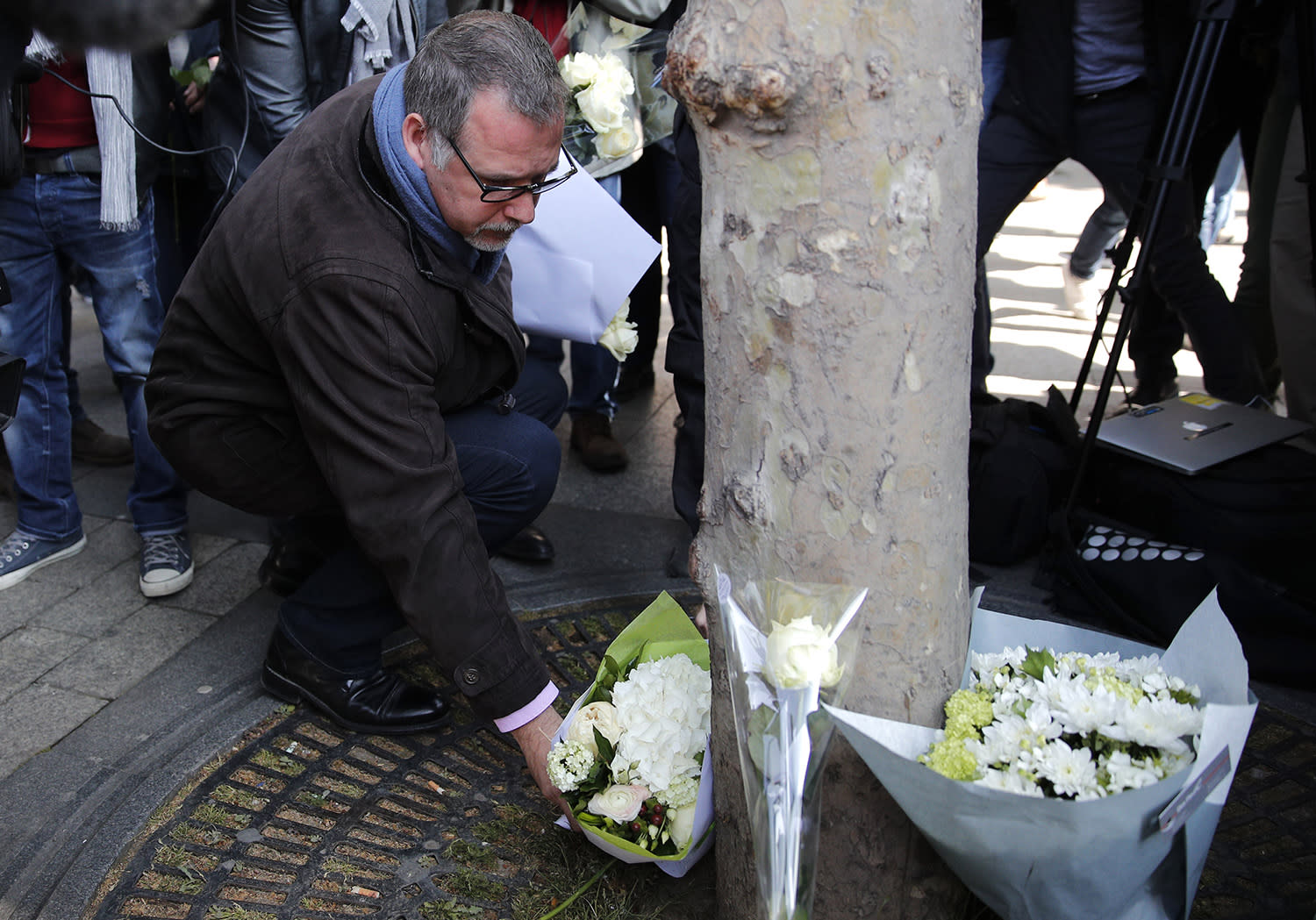 <p>Police union representative Denis Jacob lays flowers for the police officer killed in Thursday's attack, on the Champs Elysees boulevard in Paris, Friday, April 21, 2017. France began picking itself up Friday from another deadly shooting claimed by the Islamic State group, with President Francois Hollande convening the government's security council and his would-be successors in the presidential election campaign treading carefully before voting this weekend. (Photo: Christophe Ena/AP) </p>