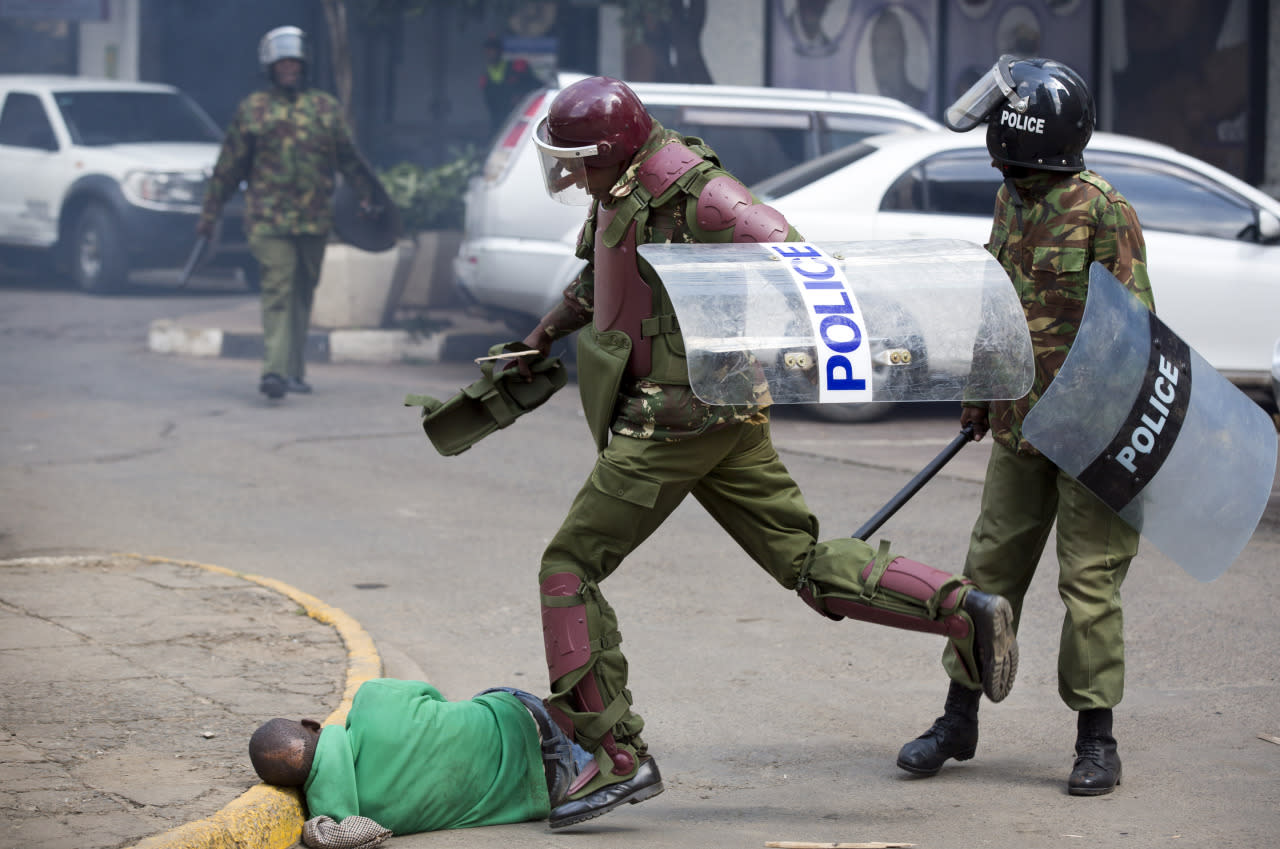 A Kenyan riot policeman repeatedly kicks a protester as he lies in the street after he tripped while trying to flee from them during a protest in downtown Nairobi, Kenya, May 16, 2016. Kenyan police have tear-gassed and beaten opposition supporters during a protest demanding the disbandment of the electoral authority over alleged bias and corruption. (AP Photo/Ben Curtis)