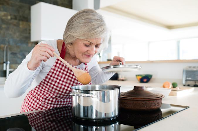 Beautiful senior woman in the kitchen cooking, mixing food in a pot, smelling it.