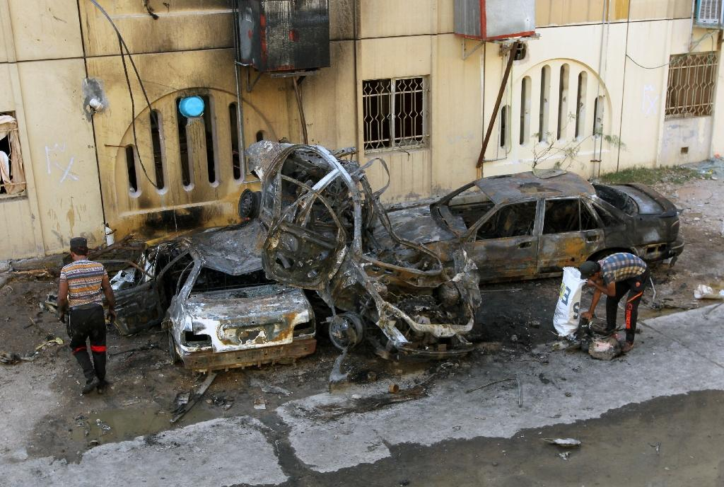 Iraqis inspect the wreckages of burnt cars on May 1, 2015 a day after a car bomb attack in the Baghdad neighbourhood of Talbiya