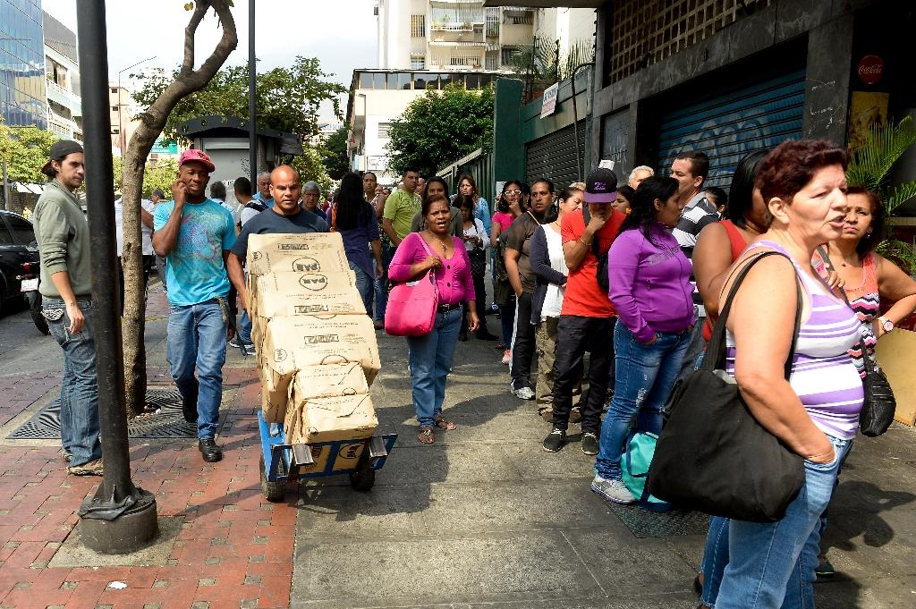 People queue outside a supermarket in Caracas where shelves are often bare in the recession-racked country