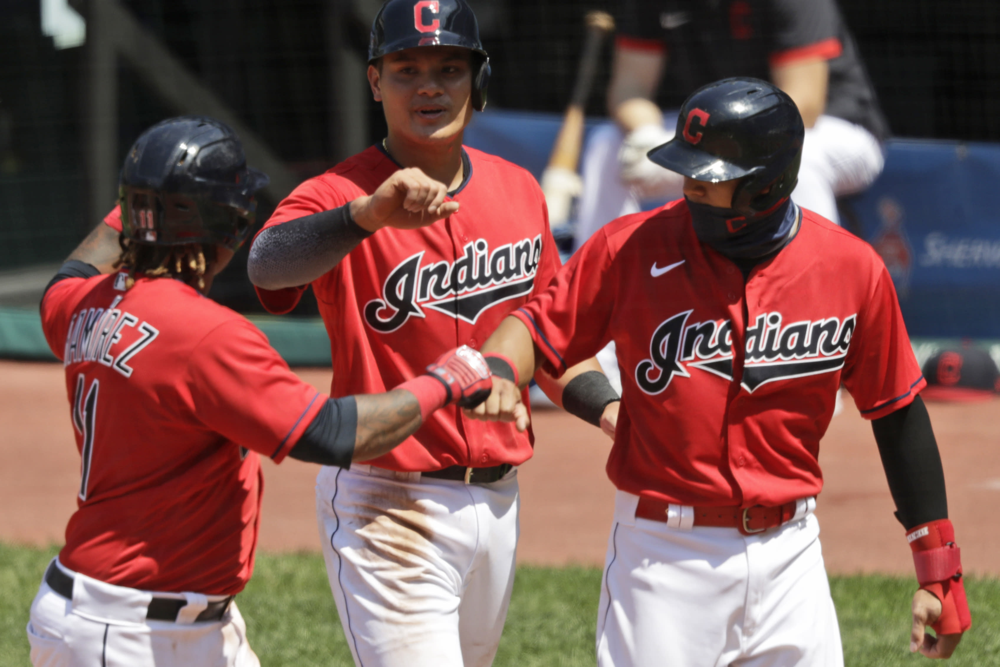 From left to right, Cleveland Indians' Jose Ramirez is congratulated by Yu Chang and Cesar Hernandez after hitting a three-run home run in the fourth inning in a baseball game against the Kansas City Royals, Sunday, July 26, 2020, in Cleveland. (AP Photo/Tony Dejak)