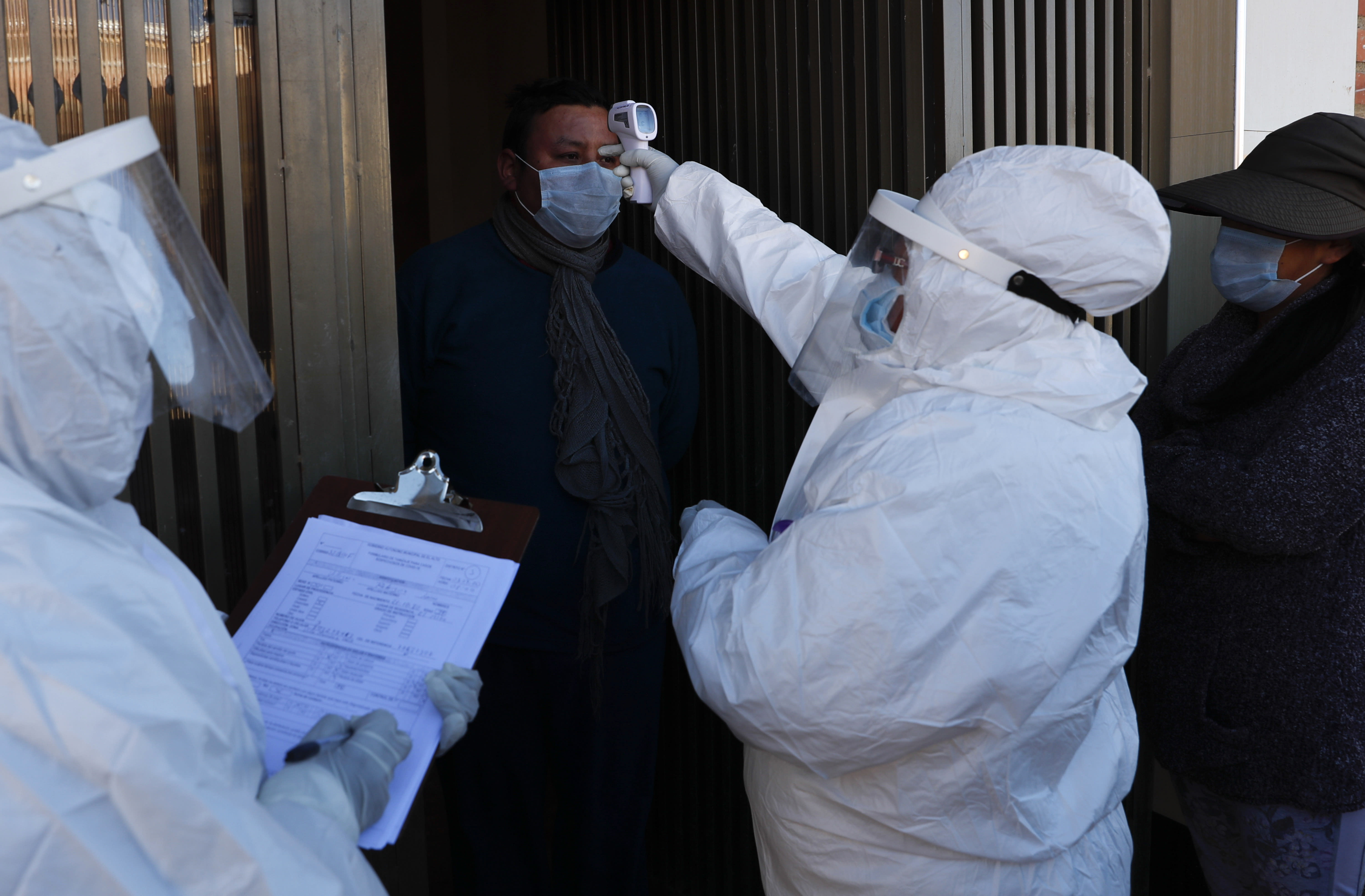 A doctor, dressed in full protective gear, measures the temperature of resident during a house-to-house new coronavirus testing campaign in the Villa Jaime Paz Zamora neighborhood of El Alto, Bolivia, Saturday, July 4, 2020. (AP Photo/Juan Karita)