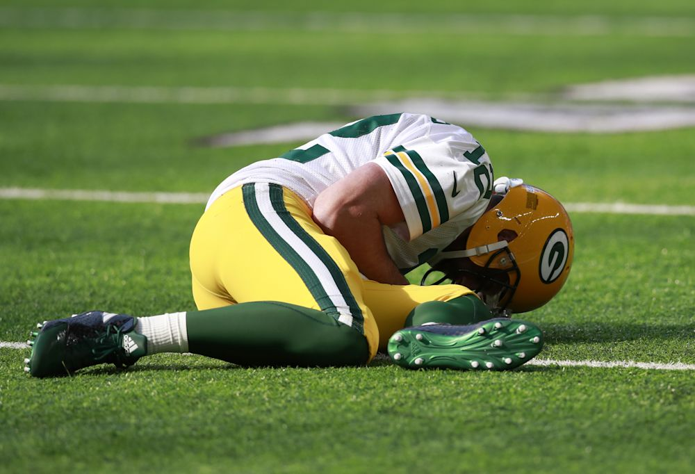 Packers quarterback Aaron Rodgers lies on the ground after being hit by Vikings outside linebacker Anthony Barr. (AP)