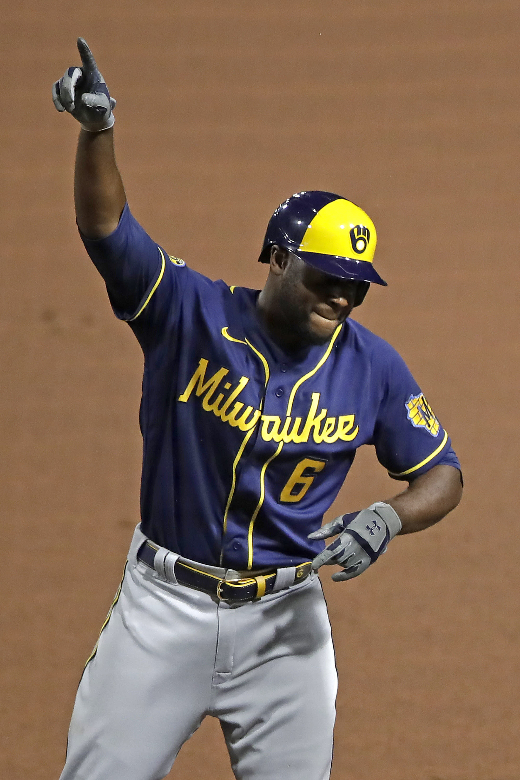 Milwaukee Brewers' Lorenzo Cain celebrates at first base after driving in a run with a single off Pittsburgh Pirates relief pitcher Nik Turley during the seventh inning of a baseball game in Pittsburgh, Monday, July 27, 2020. (AP Photo/Gene J. Puskar)