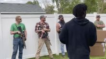 White bystanders armed with rifles watch Floyd protesters march in Indiana