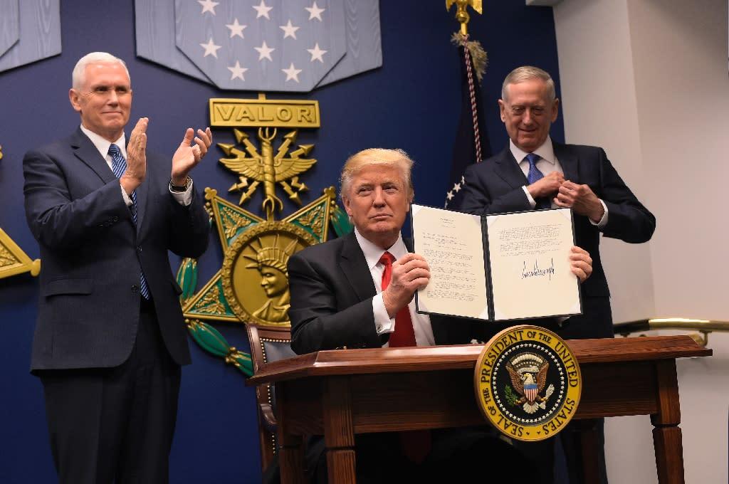 US President Donald Trump shows his signature on executive orders alongside US Defense Secretary James Mattis and US Vice President Muike Pence on January 27, 2017, at the Pentagon