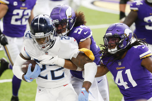 Tennessee Titans running back Derrick Henry (22) is tackled by Minnesota Vikings middle linebacker Eric Kendricks (54) and free safety Anthony Harris (41) during the first half of an NFL football game, Sunday, Sept. 27, 2020, in Minneapolis. (AP Photo/Bruce Kluckhohn)