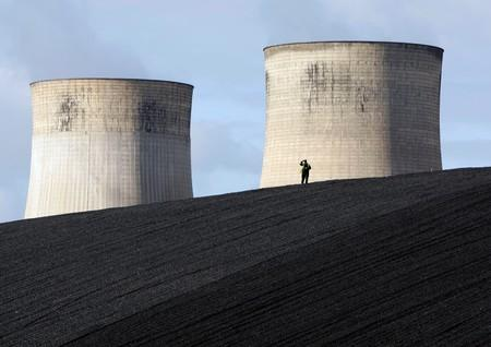 FILE PHOTO: A security guard watches from a coal heap during a climate change protest at Ratcliffe Power Station at Ratcliffe-on-Soar