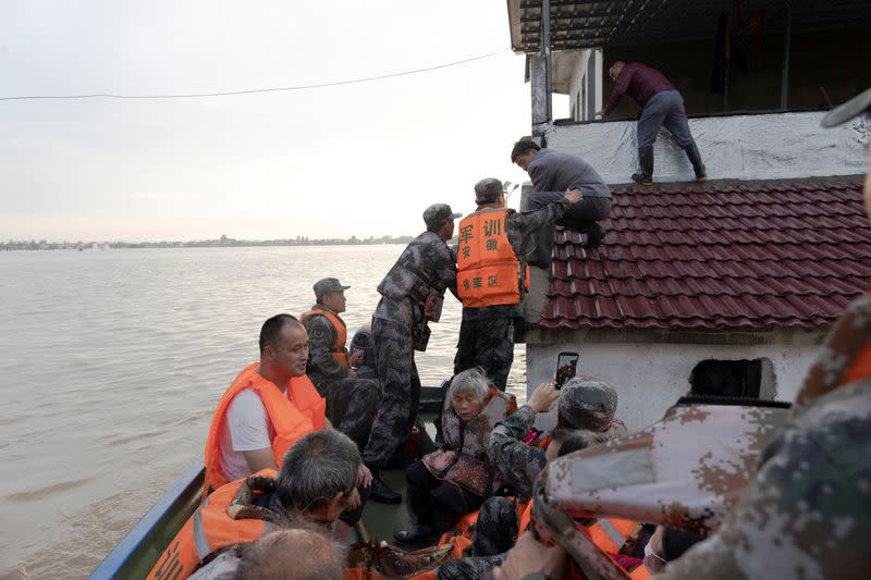 Soldiers of the PLA evacuate residents stranded by floodwaters with a boat in Luan