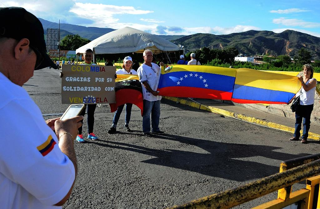 """Venezuelans pose with flags of their country and Colombia and a sign reading """"Colombia thank you for your solidarity with Venezuela"""" in San Antonio del Tachira, Venezuela on July 10, 2016 (AFP Photo/George Castellanos)"""