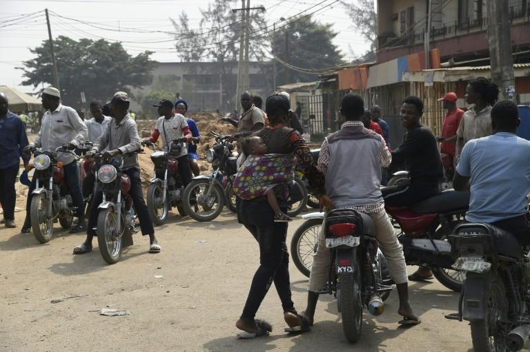 A mother and her baby try to get a ride from a motorbike taxi parked on a street in Lagos (AFP Photo/PIUS UTOMI EKPEI)