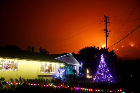 People stand on a roof of a home illuminated with Christmas lights to watch wildfire on a hillside burn during the Thomas Fire in Santa Barbara county near Carpinteria, California. REUTERS/Patrick T Fallon