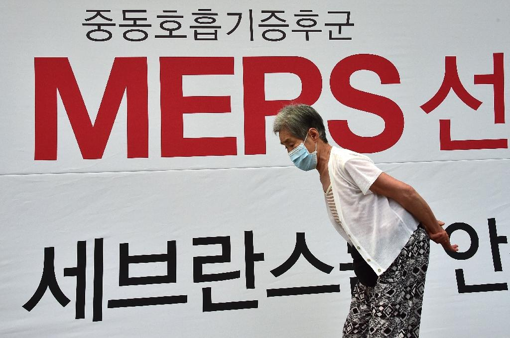 An elderly woman walks past signage on MERS at Severance Hospital in Seoul on June 16, 2015 (AFP Photo/Jung Yeon-Je)