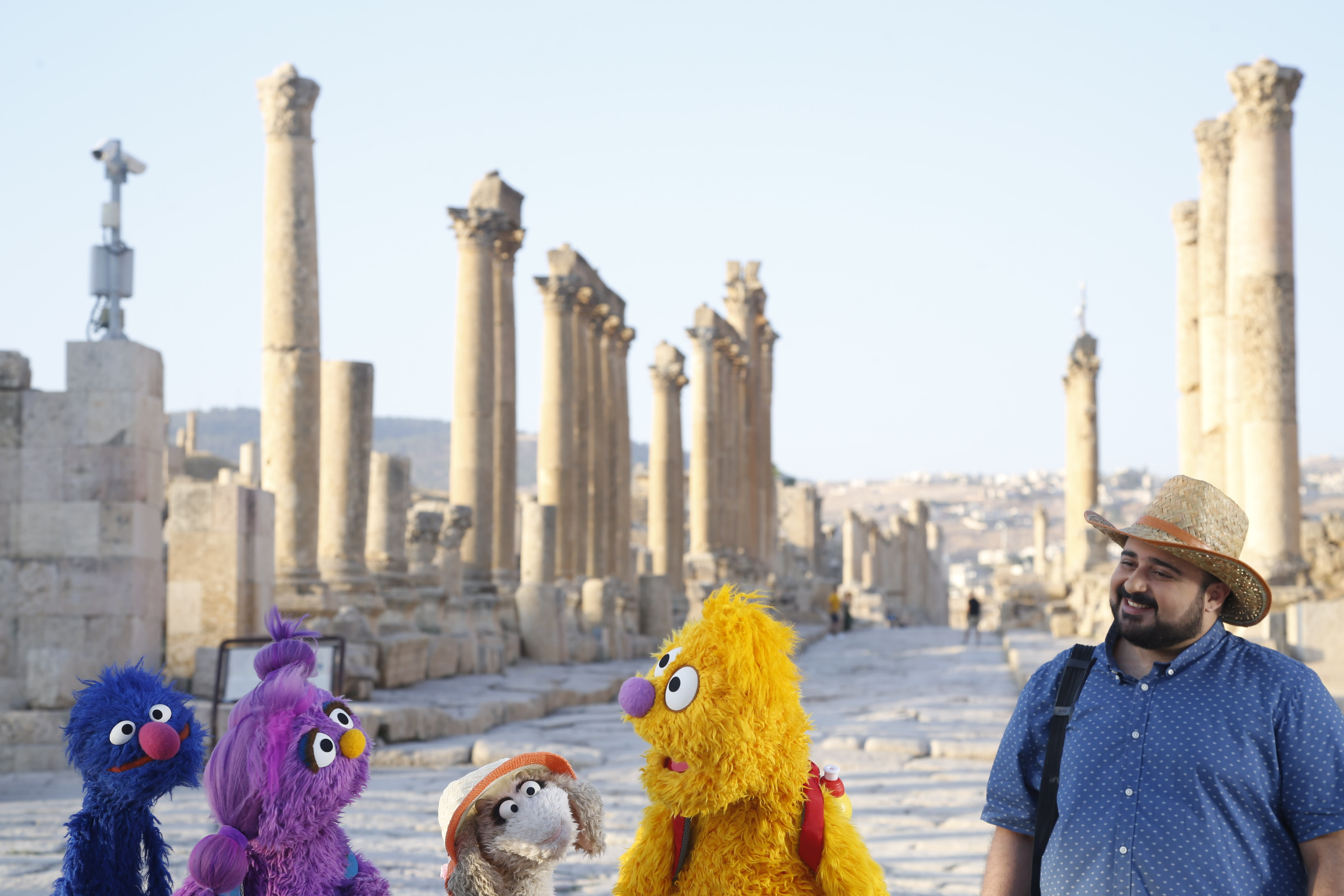 """This image released by Sesame Workshop shows, from left, Grover, Basma, Ma'zooza and Jad with Rami Delshad, who portrays Hadi in """"Welcome Sesame,"""" a new, locally produced Arabic TV program for the hundreds of thousands of children dealing with displacement in Syria, Iraq, Jordan and Lebanon. (Sesame Workshop via AP)"""