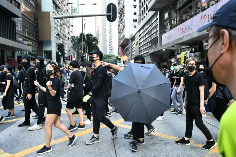 Crowds of black-clad protesters, many wearing face masks despite a recent ban, filled Hong Kong's Causeway Bay (AFP Photo/Anthony WALLACE)