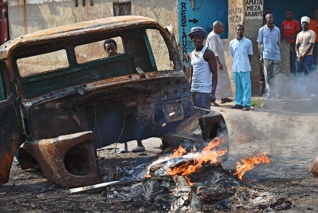 Protestors opposed to Burundian President Pierre Nkurunziza's third term stand beside a burning vehicle during a demonstration in Bujumbura on May 26, 2015