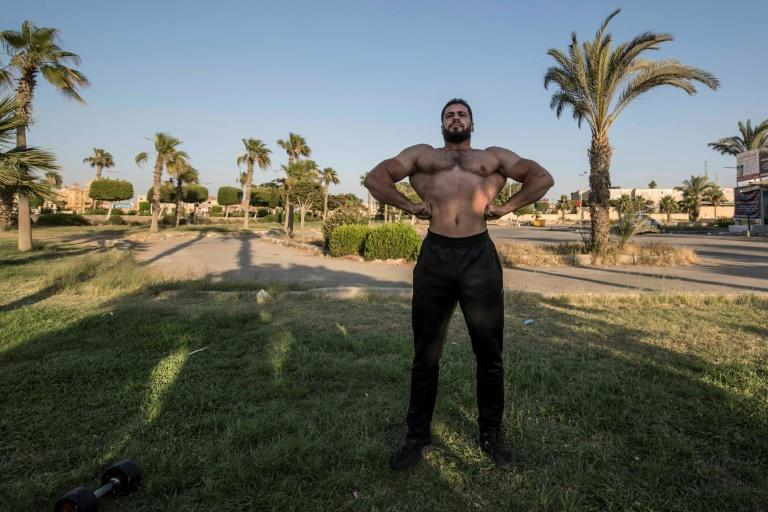 Bodybuilder coach, a 33-year-old Syrian exile who settled in Cairo after escaping his war-torn country with the start of the conflict in 2011, takes part in a training in the 6th of October city in Giza governorate, Egypt. (AFP Photo/Khaled DESOUKI)