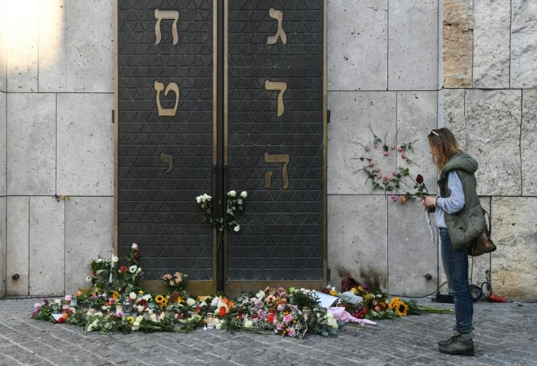A woman stands next to flowers laid next to the entrance of the synagogue in Munich, dring a protest against anti-Semitism on October 11, 2019 two days after a deadly shooting during an attack in Halle targeting a Turkish restaurant after an attempt at the synagogue.Jews in Germany prepared to mark the Sabbath Friday with their confidence in the community's miraculous rebirth shaken by the deadly anti-Semitic rampage in Halle on Yom Kippur