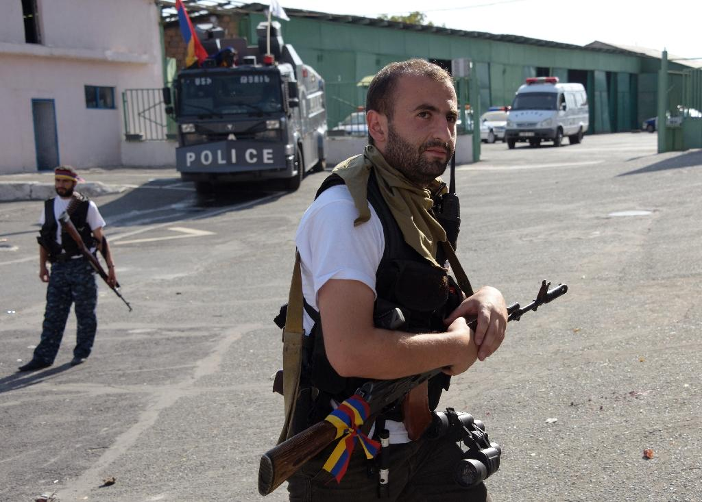 Armed man stand outside a police vehicle after they released the final four police officers held captive in the Armenian capital Yerevan on July 23, 2016