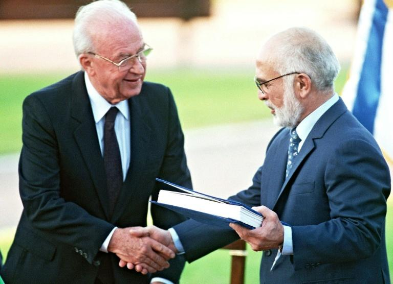 Jordan's King Hussein (R) and Israeli Premier Yitzhak Rabin shake hands after exchanging the documents of the peace treaty on the southern shore of the Sea of Galilee (AFP Photo/SVEN NACKSTRAND)