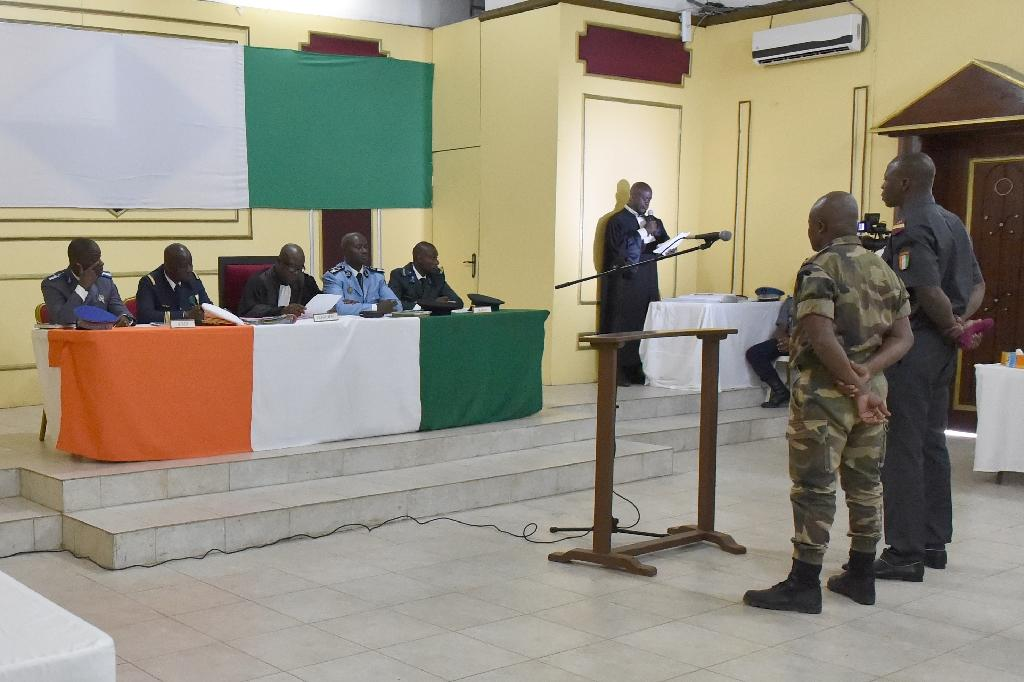 """Two Ivorian soldiers who worked alongside jihadists who helped to organize the attack on the resort of Grand Bassam in March 2016 and who are accused of """"violation of military rules"""" are questioned at the beginning of their trial on August 4, 2016"""