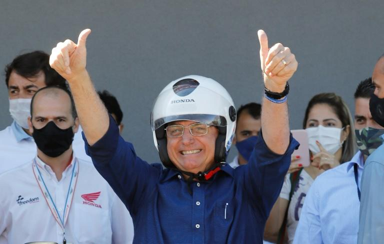 Brazilian President Jair Bolsonaro gestures after going out for a motorcycle ride following a negative test result for coronavirus, which he was diagnosed with earlier this month (AFP Photo/Sergio LIMA)