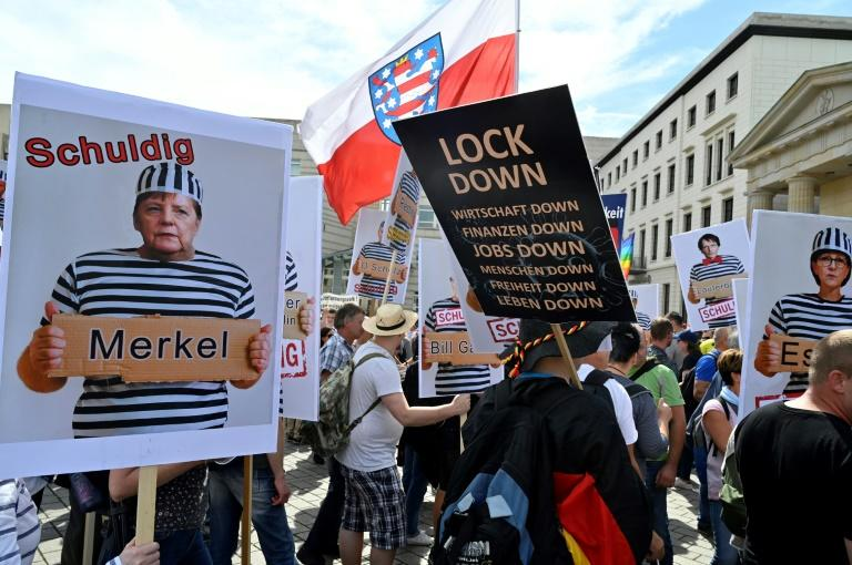 Protesters carried placards featuring German chancellor Angela Merkel as a prisoner