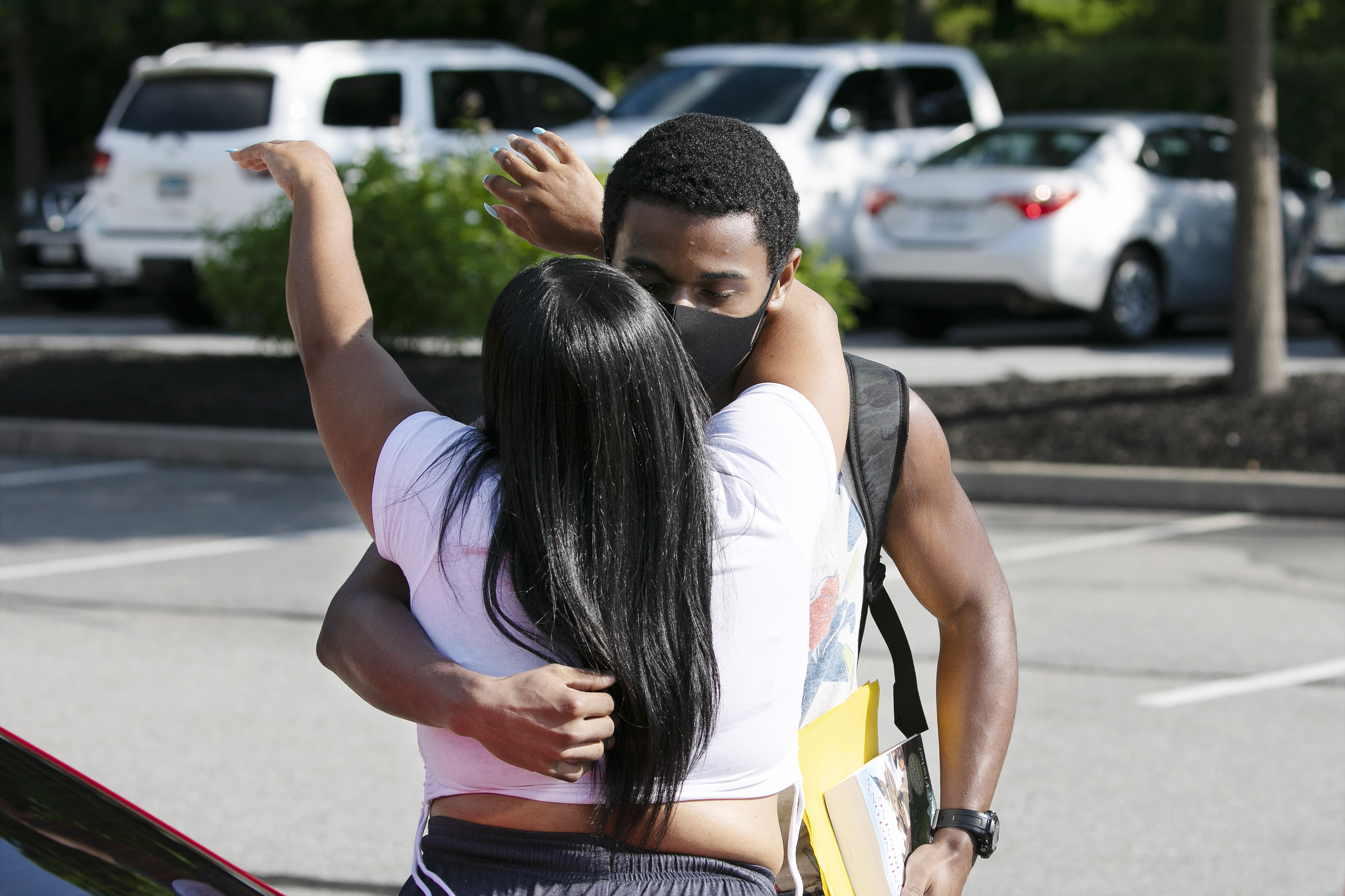 Cadet candidate Walter Thomas Pack, Jr., of Philadelphia, gets a goodbye hug from his mother Kathy as she drops him off at the U.S. Military Academy, Monday, July 13, 2020, in West Point, N.Y. The Army is welcoming more than 1,200 candidates from every state. Candidates will be COVID-19 tested immediately upon arrival, wear masks, and practice social distancing. (AP Photo/Mark Lennihan)