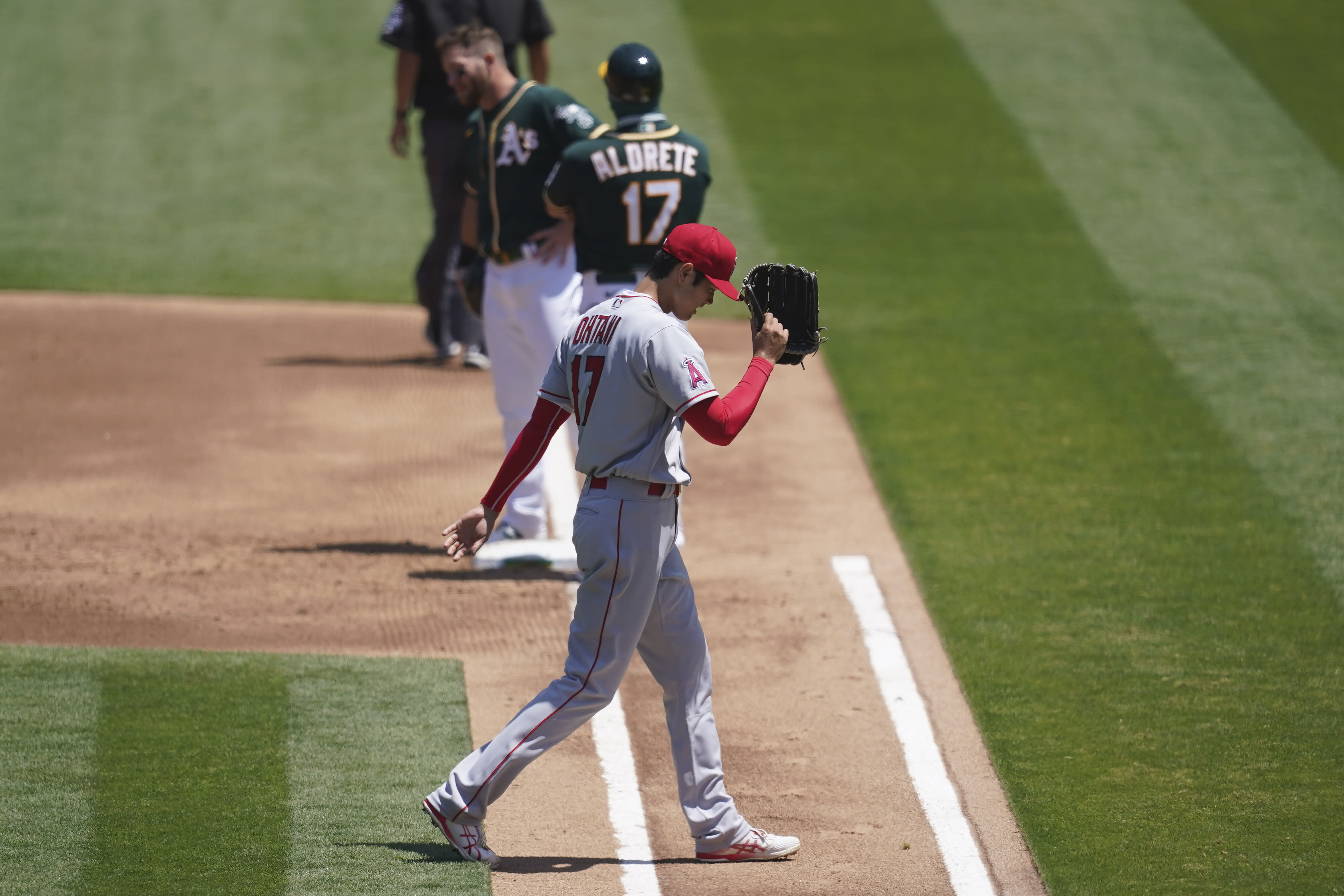 Los Angeles Angels' Shohei Ohtani (17) walks toward the dugout after being relieved during the first inning of a baseball game against the Oakland Athletics in Oakland, Calif., Sunday, July 26, 2020. Athletics' Robbie Grossman, top left, hit an RBI-single. (AP Photo/Jeff Chiu)
