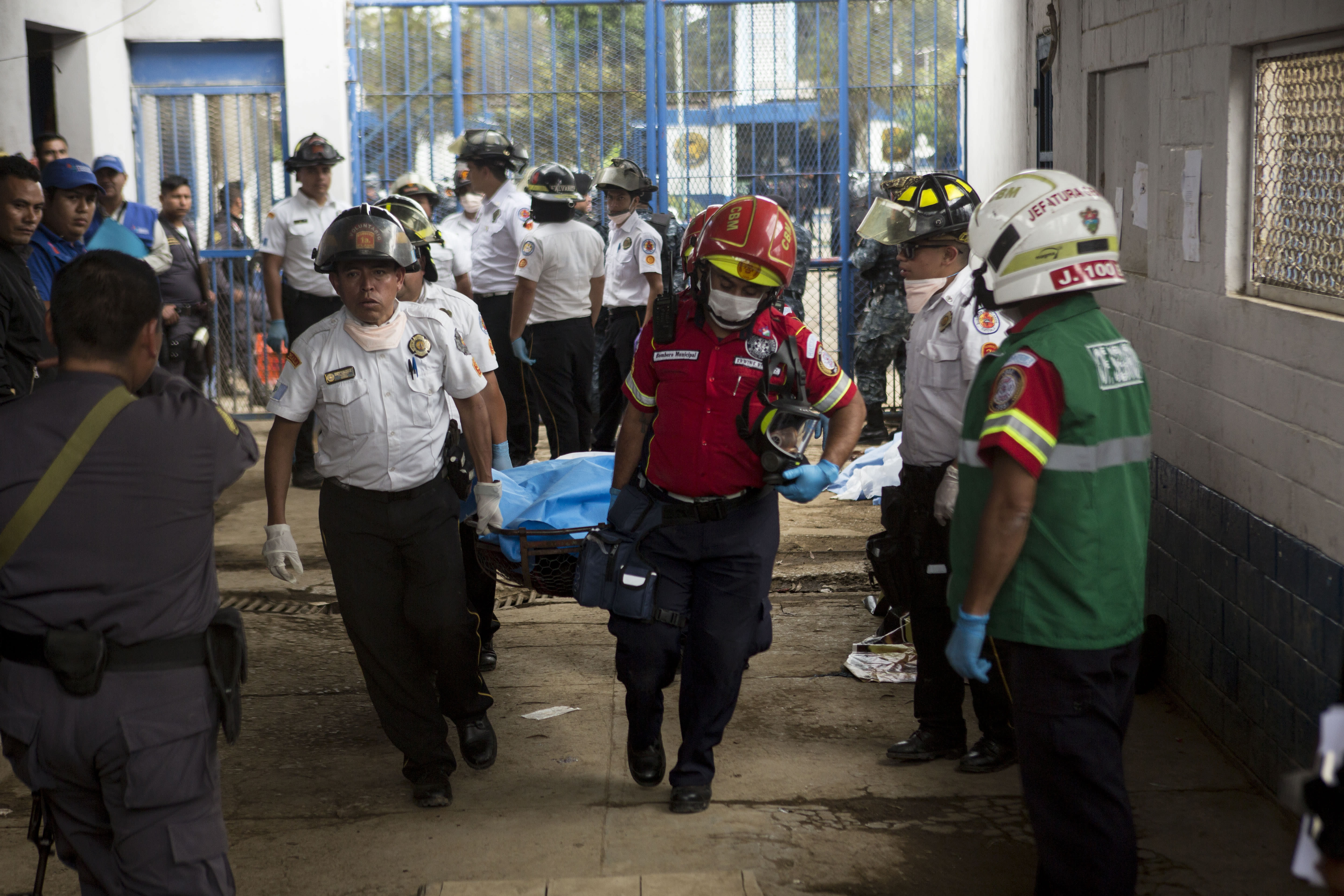 Firefighters carry the body of an inmate who died during a shooting inside the Pavon Rehabilitation Model Farm in Fraijanes, Guatemala, Tuesday, May 7, 2019. At least three people were killed and 10 people were wounded in the shooting, authorities said. (AP Photo/Oliver De Ros)