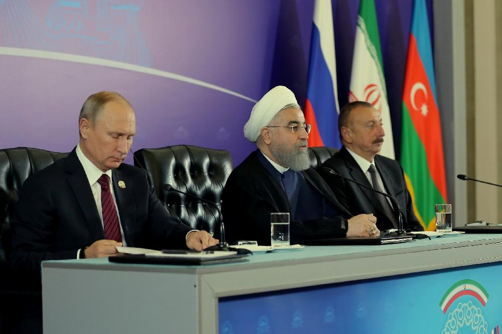 A handout photo provided by the office of Iranian President Hassan Rouhani shows him (C) holding a press conference with Azerbaijan's President Ilham Aliyev (R) and Russian President Vladimir Putin (L) following a meeting in Tehran on November 1, 2017. (AFP Photo/HO)