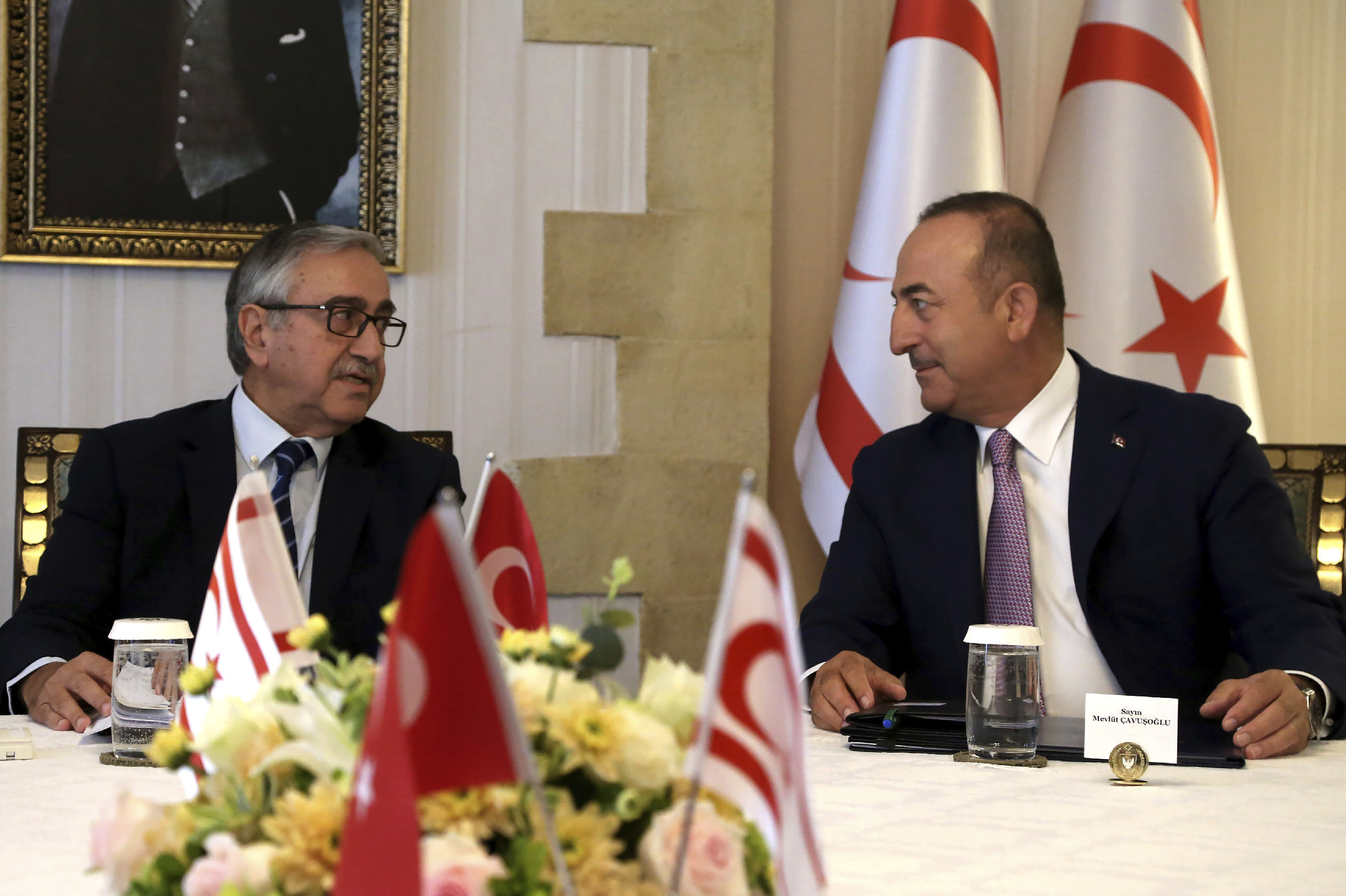 Turkish Foreign Minister Mevlut Cavusoglu, right, talks with Turkish Cypriot leader Mustafa Akinci during a meeting in the Turkish occupied area in the northern part of divided capital Nicosia, Cyprus, Monday, Sept. 9, 2019. Cavusoglu is in the northern part of divided Cyprus for three-day visit. (AP Photo/Petros Karadjias)