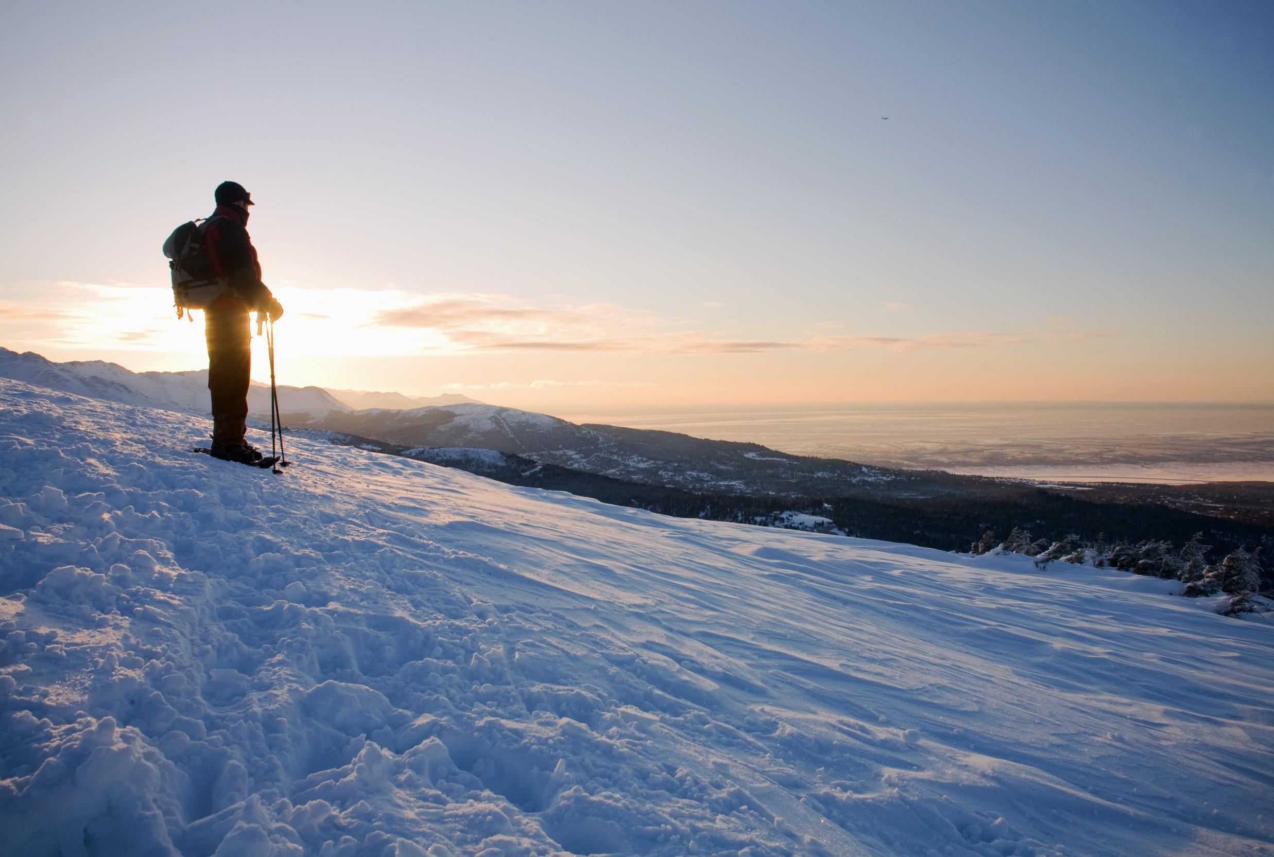 A cross country skier takes in the view from the hills of Glen Alps overlooking Anchorage, Alaska.