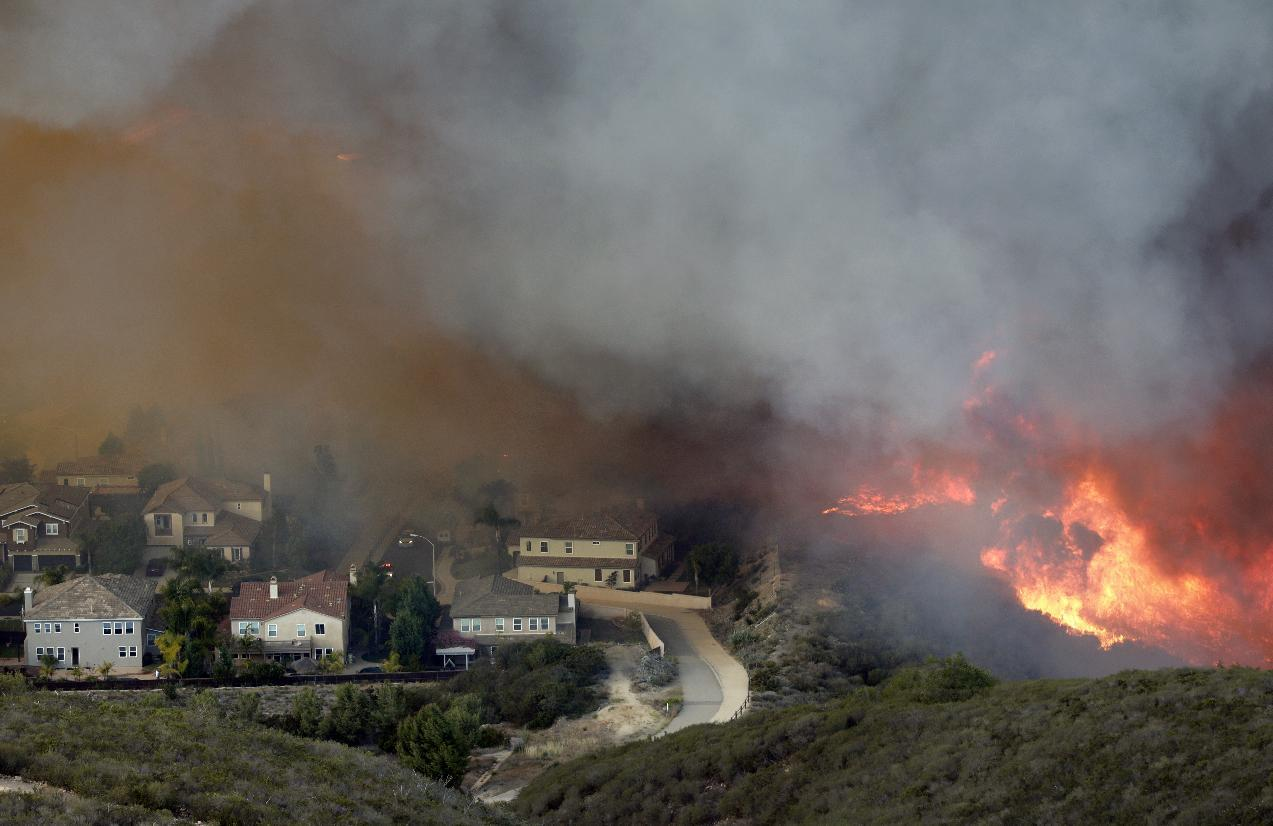A wildfire approaches homes on Wednesday, May 14, 2014, in San Marcos, Calif. Flames engulfed suburban homes and shot up along canyon ridges in one of the worst of several blazes that broke out Wednesday in Southern California during a second day of a sweltering heat wave, taxing fire crews who fear the scattered fires mark only the beginning of a long wildfire season. (AP Photo/)