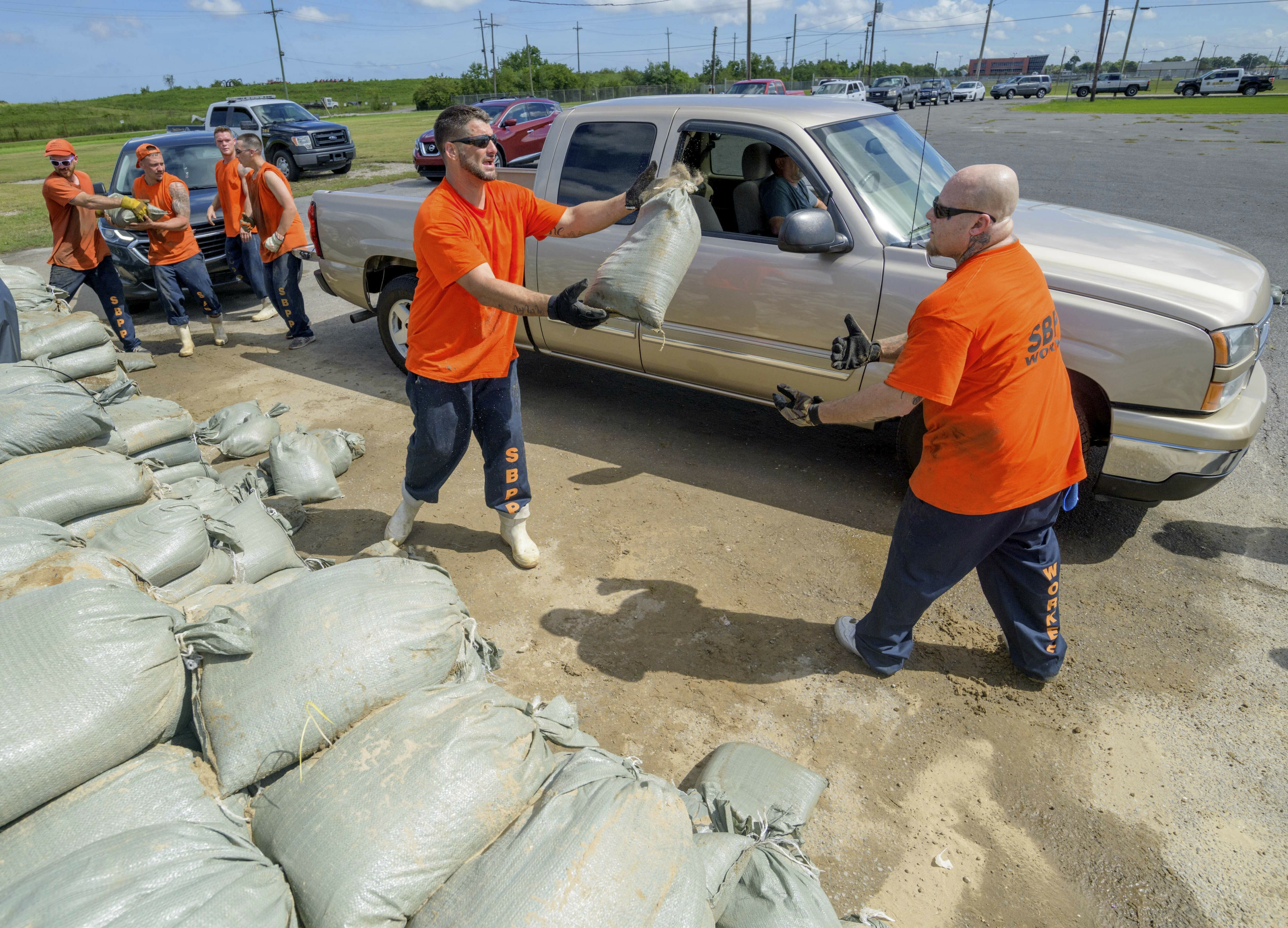 St. Bernard Parish Sheriff's Office inmate workers move free sandbags for residents in Chalmette, La., Thursday, July 11, 2019 ahead of ahead of Tropical Storm Barry from the Gulf of Mexico. (AP Photo/Matthew Hinton)