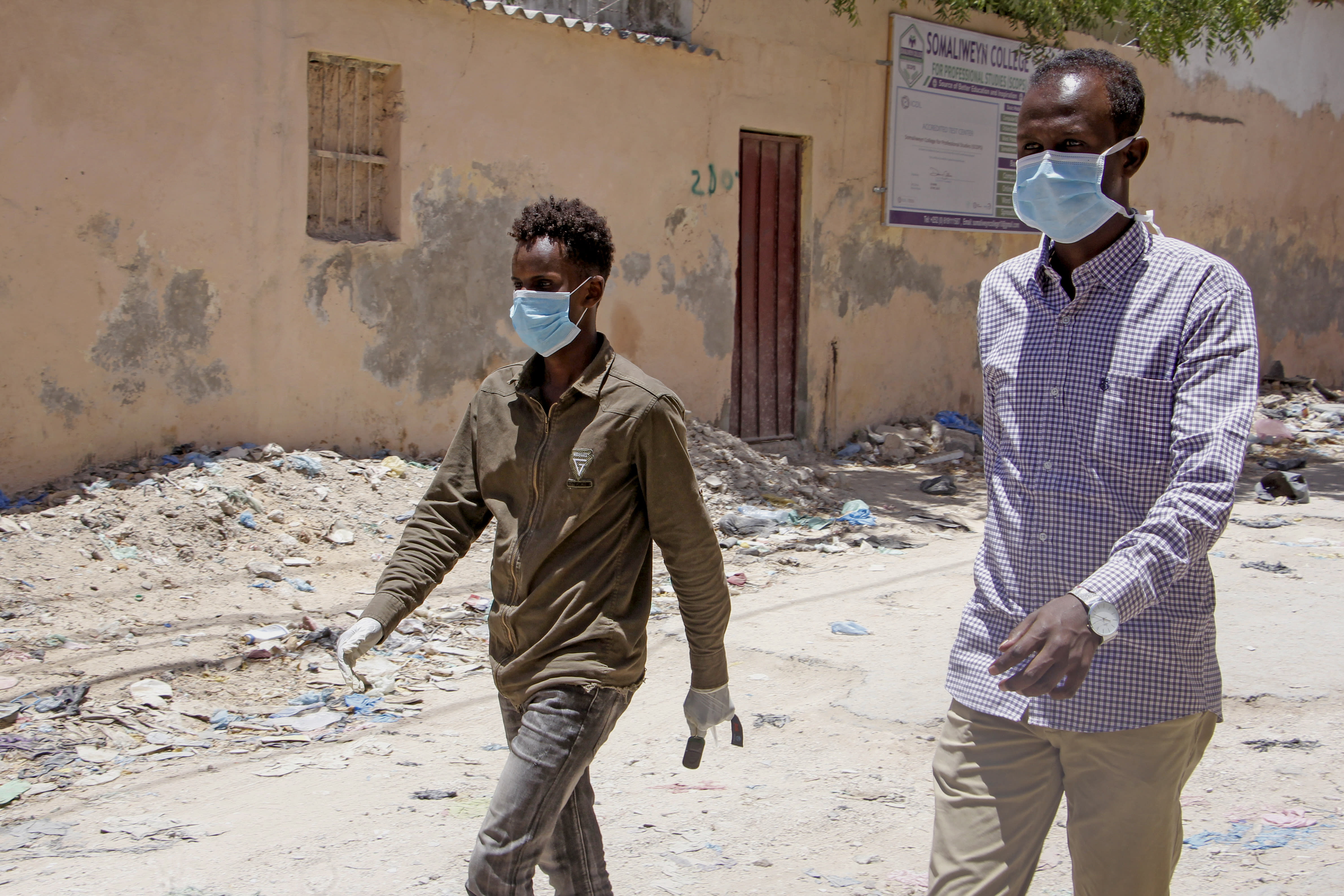 Somali men wear surgical masks on the street after after the government announced the closure of schools and universities and banned large gatherings, following the announcement on Monday of the country's first case of the new coronavirus, in the capital Mogadishu, Somalia Wednesday, March 18, 2020. For most people, the new coronavirus causes only mild or moderate symptoms such as fever and cough and the vast majority recover in 2-6 weeks but for some, especially older adults and people with existing health issues, the virus that causes COVID-19 can result in more severe illness, including pneumonia. (AP Photo/Farah Abdi Warsameh)