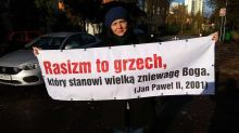 Polish Woman Says She Was Dragged Out Of Church After Unfurling Anti-Racism Banner