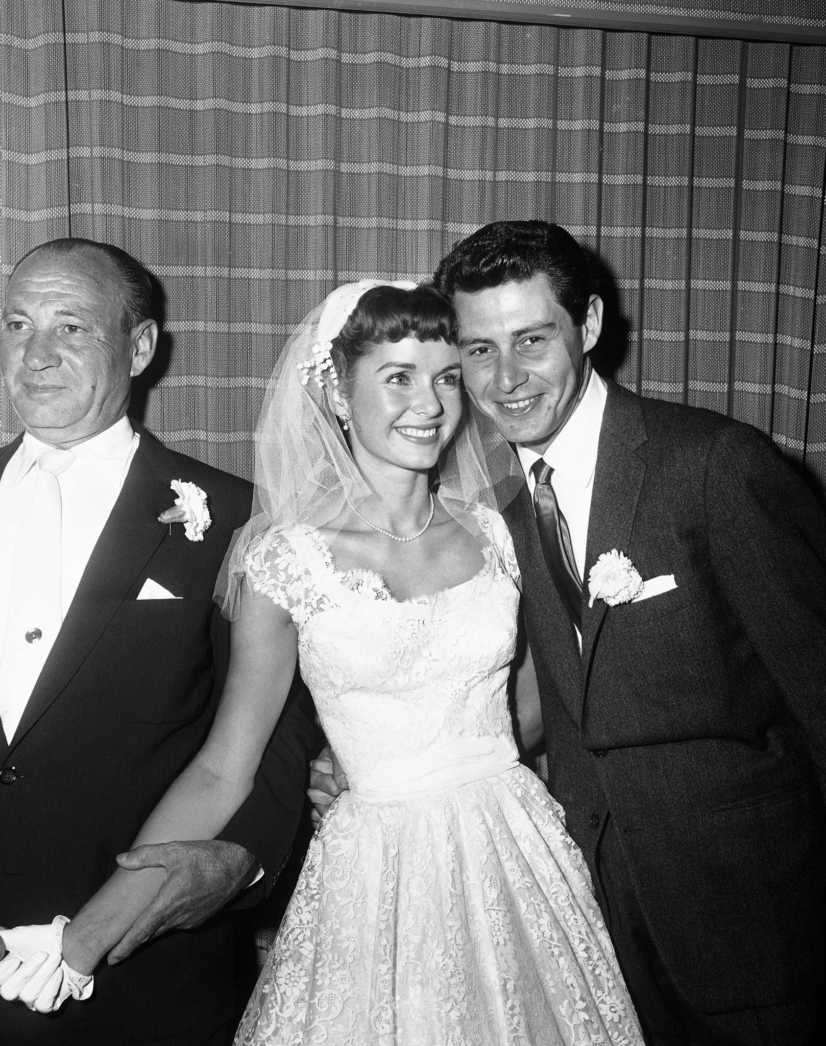 <p>Singer Eddie Fisher, 26, and his bride, actress Debbie Reynolds, 23, pose cheek to cheek following their marriage in a civil ceremony at Grossinger's Catskills Resort in Liberty, N.Y.,, Sept. 26, 1955. The man at left is unidentified. (AP Photo/Marty Lederhandler) </p>