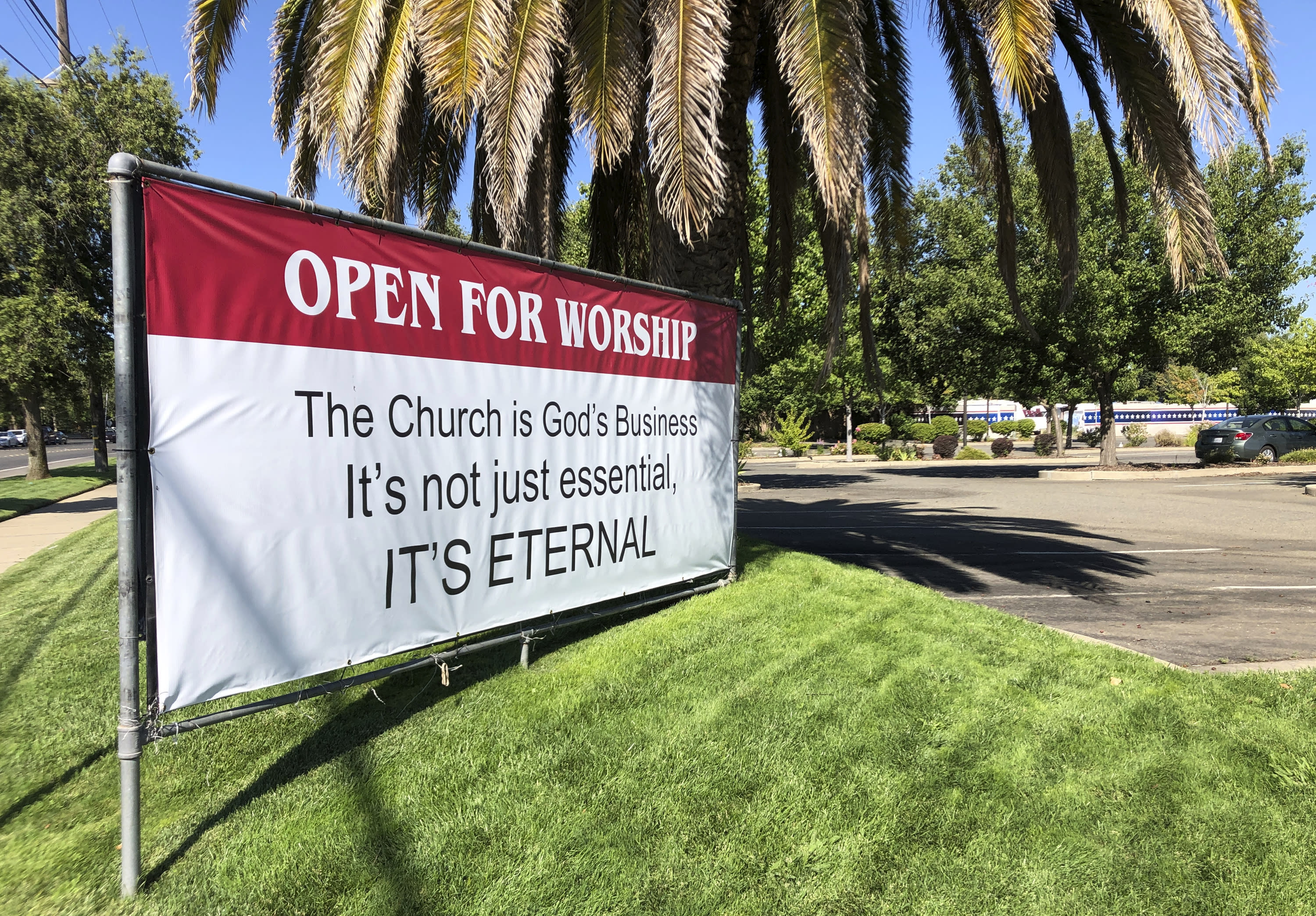 """An """"Open for Worship"""" banner is posted outside the Crossroads Community Church in Yuba City, Calif., Thursday, July 9, 2020. Sutter County was one of the first counties to reopen its economy when it defied Gov. Gavin Newsom's stay-at-home order in May to allow restaurants, hair salons, gyms and shopping malls to reopen. But Thursday, the county was added to a state watch list because of its rising number of coronavirus cases and hospitalizations. (AP Photo/Adam Beam)"""