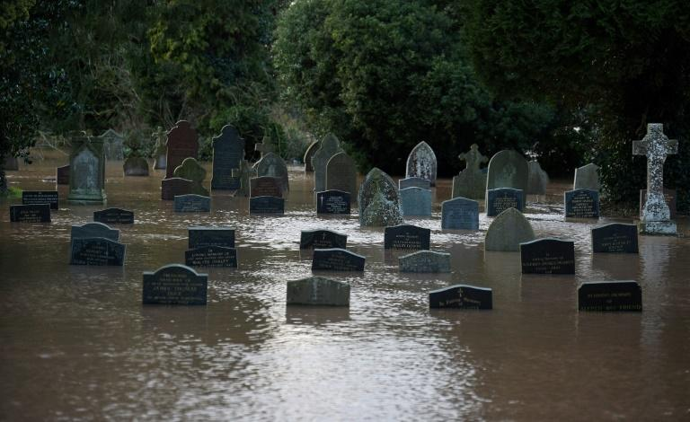 Flood water surrounds grave stones in a graveyard in Tenbury Wells, after the River Teme burst its banks in western England after Storm Dennis caused flooding across large swathes of Britain (AFP Photo/Oli SCARFF )