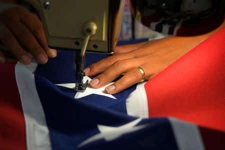 Blanca Hernandez sews stars on a Confederate Battle Flag in the Alabama Flag & Banner shop in Huntsville, Alabama, U.S., August 24, 2017. REUTERS/Harrison McClary