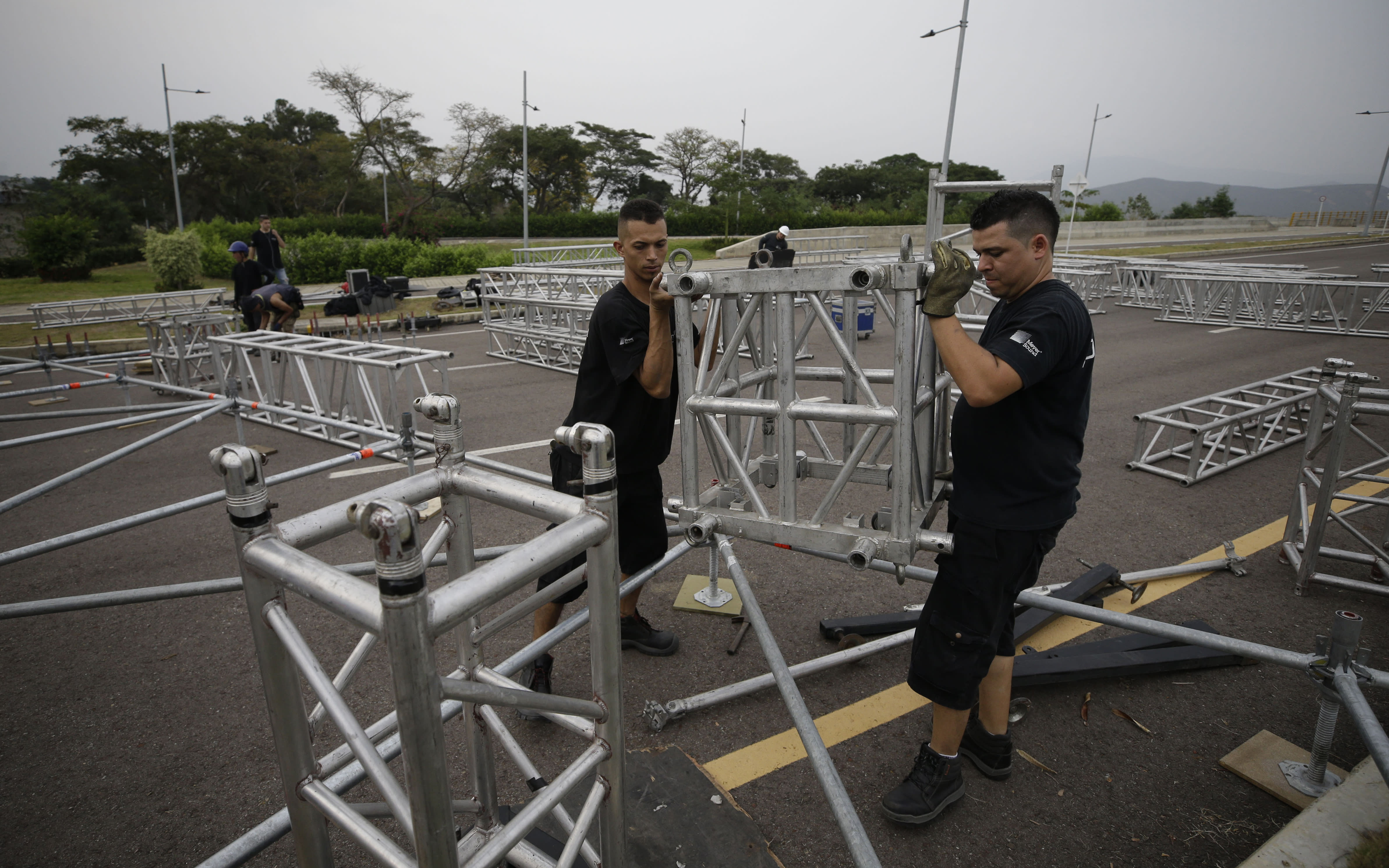 "Workers build the stage for the upcoming ""Venezuela Aid Live"" concert at the Tienditas International Bridge on the outskirts of Cucuta, Colombia, on the border with Venezuela, Monday, Feb. 18, 2019. Billionaire Richard Branson is organizing the concert on Feb. 22 featuring Spanish-French singer Manu Chao, Mexican band Mana, Spanish singer-songwriter Alejandro Sanz and Dominican artist Juan Luis Guerra. (AP Photo/Fernando Vergara)"
