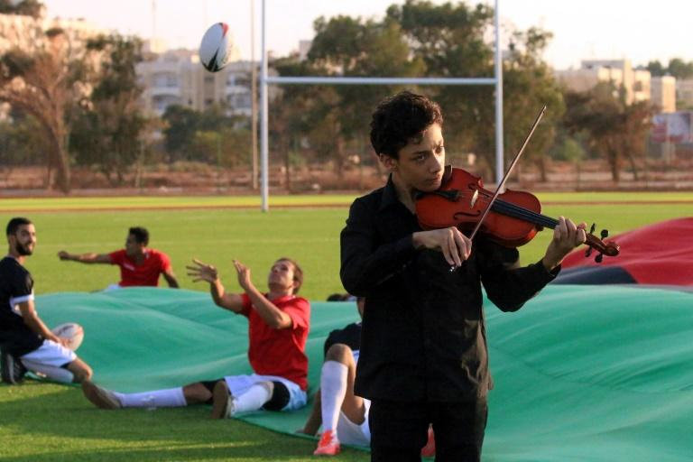 A Libyan youth plays the violin at the opening of the first rugby field at the University of Benghazi, which was built as part of the United Nations Office Development Programme