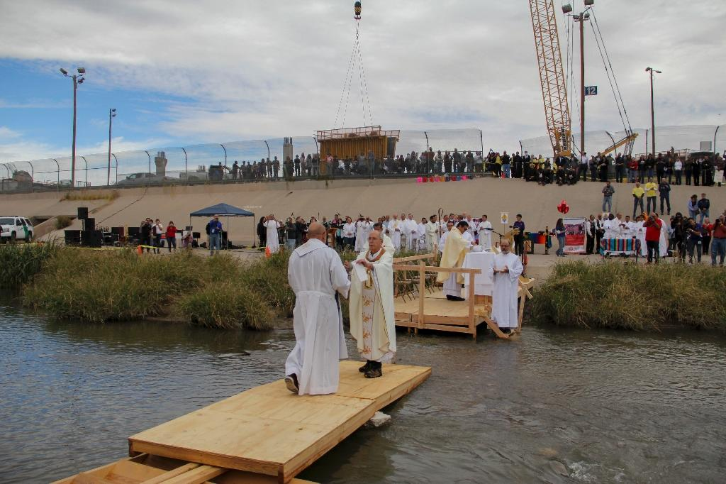 Catholic priests from Mexico (L) and the US (R) meet on November 4, 2017 at the Rio Grande during a binational border mass by hundreds of Catholics from both countries in memory of migrants killed while crossing the river trying to reach the US (AFP Photo/HÉRIKA MARTÍNEZ)