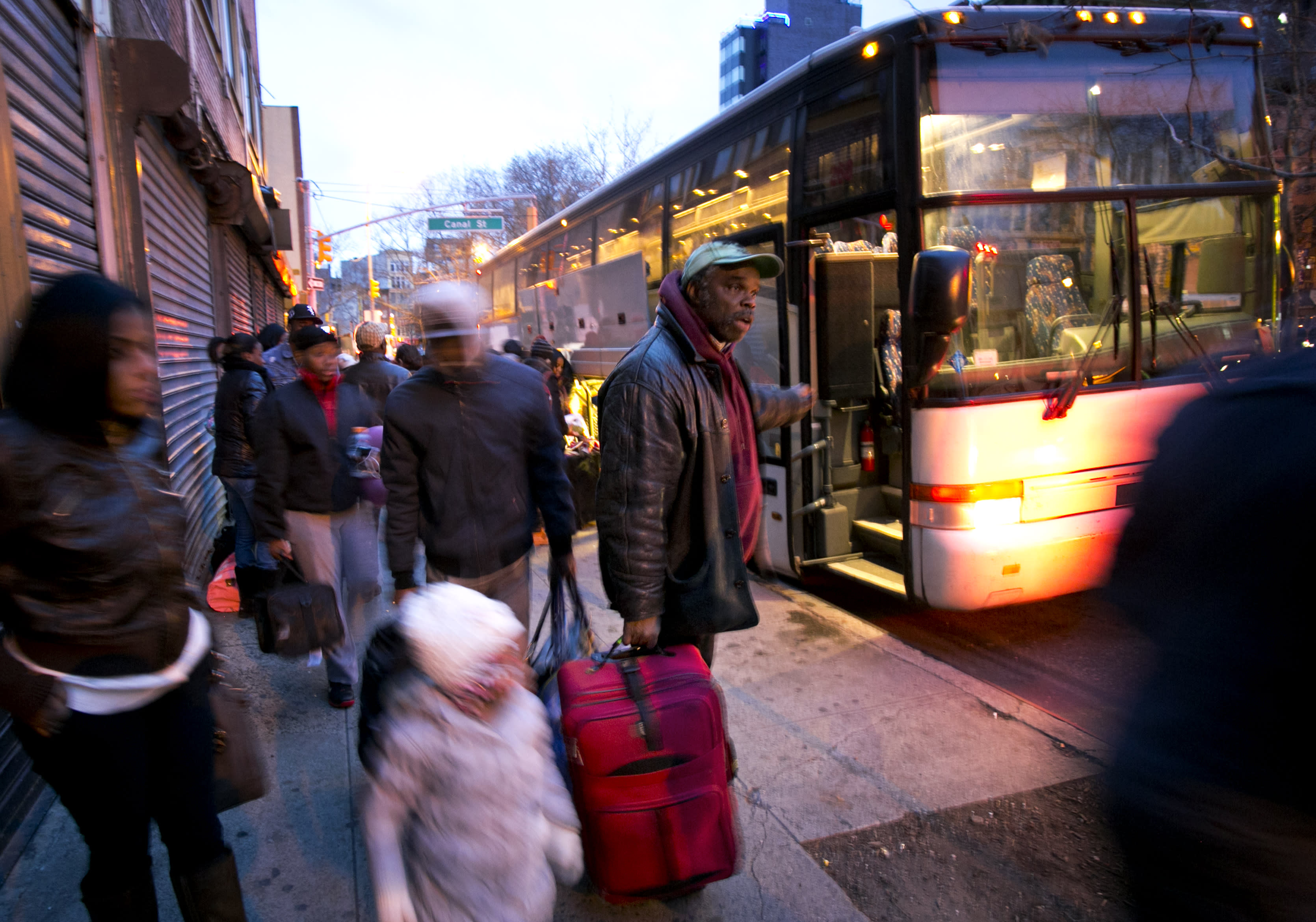 Travelers who arrived on a bus from Virginia pull their suitcases along a sidewalk in the Chinatown section of New York, Tuesday, Nov. 26, 2013. Millions of Americans are hurtling along the nation's jumble of transportation arteries for Thanksgiving, and more of them are discovering that a bus is the cheapest, comfiest and coolest way to stay zen while completing the nation's largest annual human migration. (AP Photo/Mark Lennihan)