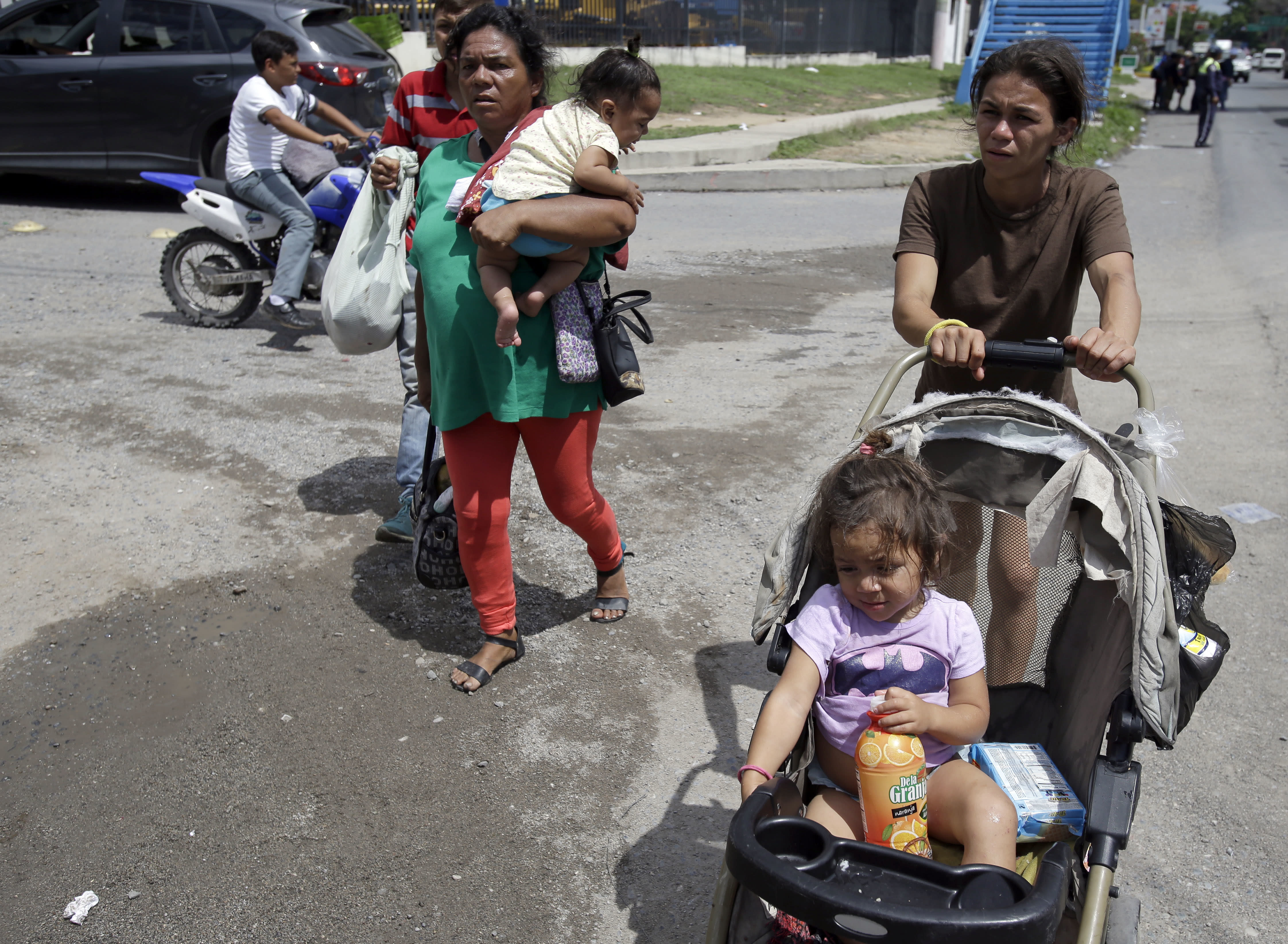 A couple of Hondruasn migrant mothers carry their children as they continue on their trek to the United States, in Teculutan, Guatemala, Wednesday, Oct. 17, 2018. The group of some 2,000 Honduran migrants hit the road in Guatemala again Wednesday, hoping to reach the United States despite President Donald Trump's threat to cut off aid to Central American countries that don't stop them. (AP Photo/Moises Castillo)