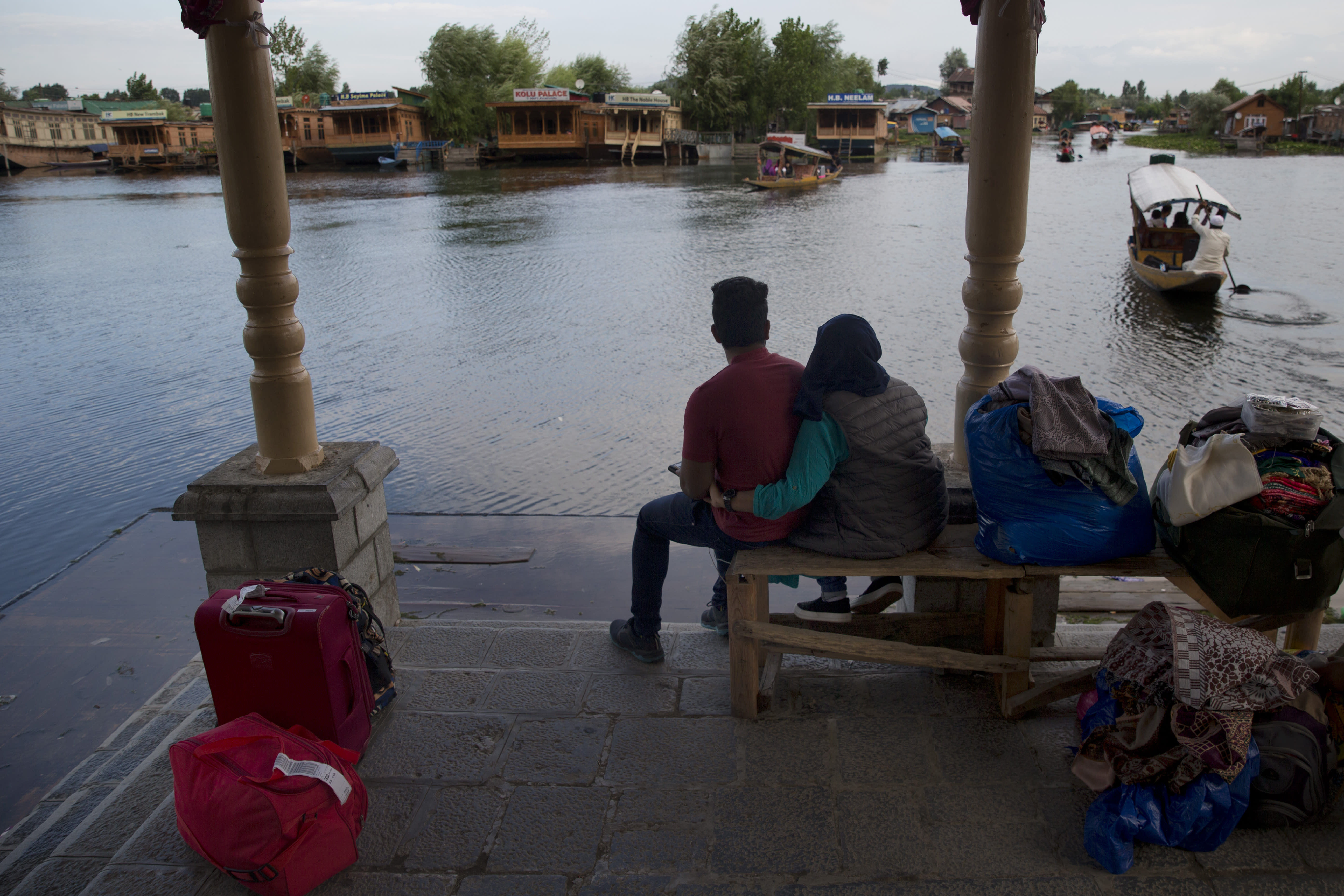 FILE - In this Saturday, Aug. 3, 2019, file photo, an Indian couple waits for transport as they prepare to leave Srinagar, Indian controlled Kashmir. Authorities in Indian-controlled Kashmir are allowing tourists back into the region two months after ordering them to leave, citing security concerns. The local government had instructed tourists and Hindu pilgrims to leave on Aug. 2, three days before India stripped the Muslim-majority region of its statehood and special semi-autonomous status. (AP Photo/Dar Yasin, File)