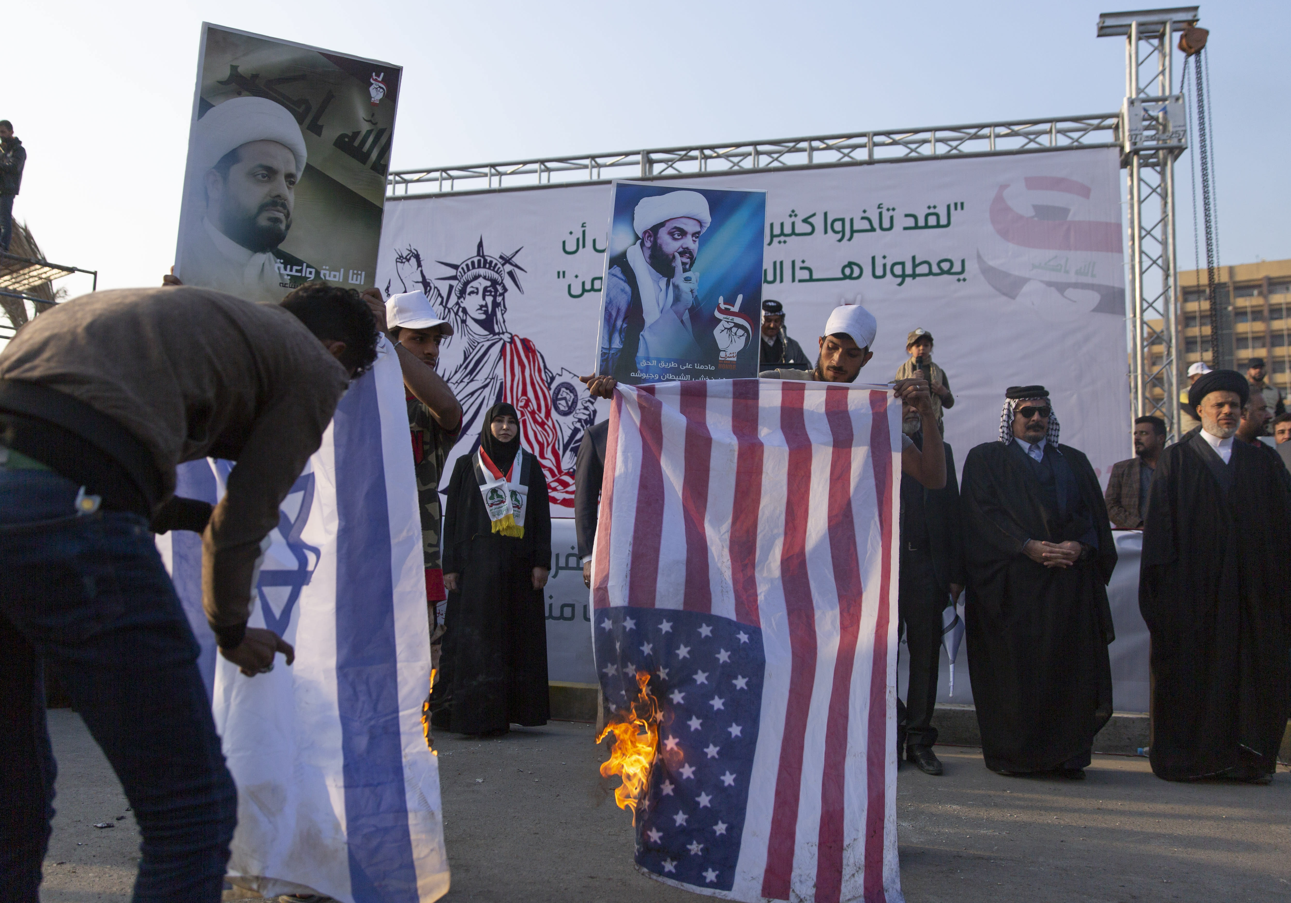 Protesters burn Israeli and US flags while others carry posters with pictures of Qais al-Khazali, during a rally for the Shiite group Asaib Ahl al-Haq, in Baghdad, Iraq, Saturday, Dec. 14, 2019. (AP Photo/Nasser Nasser)